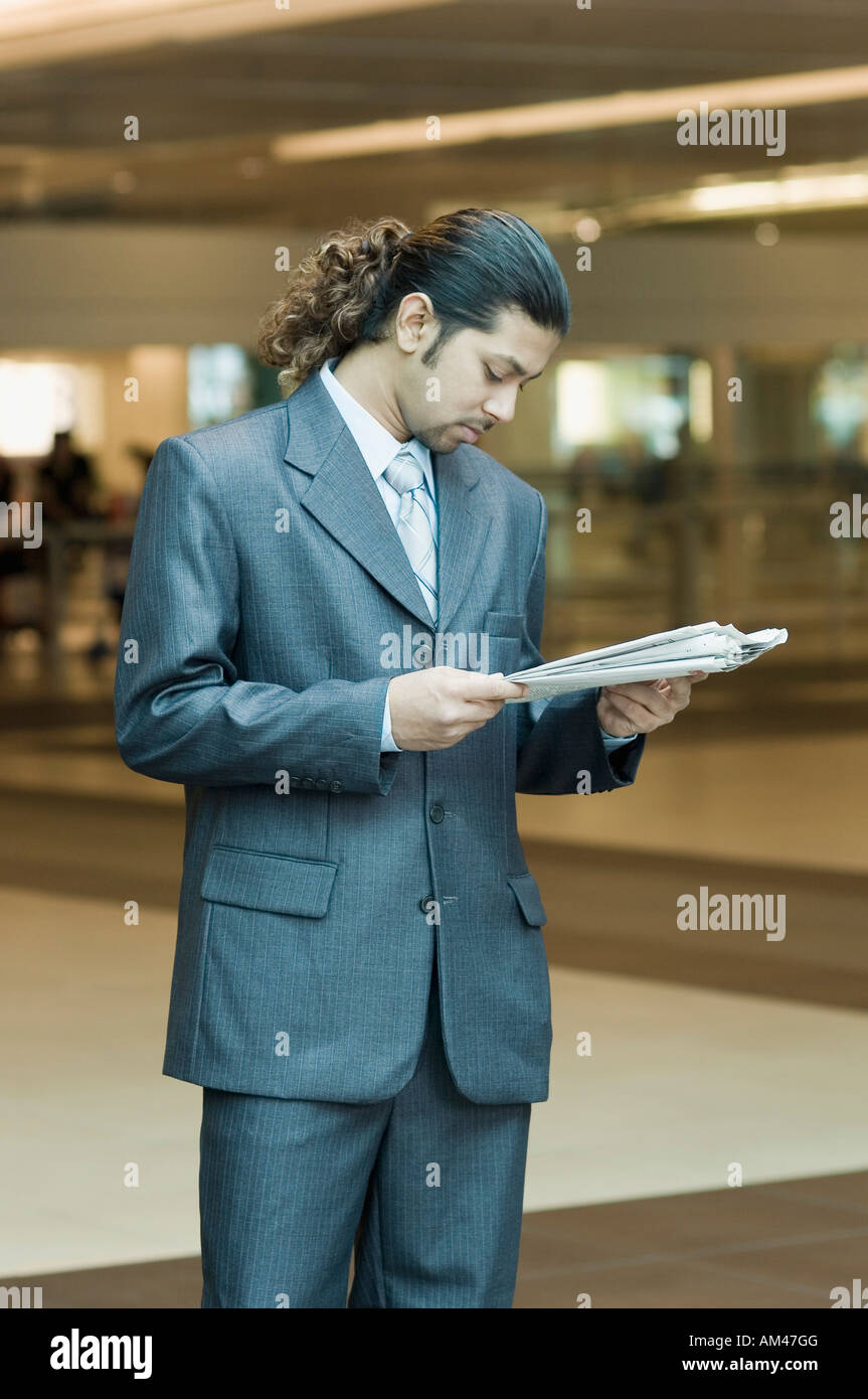 Businessman reading a newspaper - Stock Image