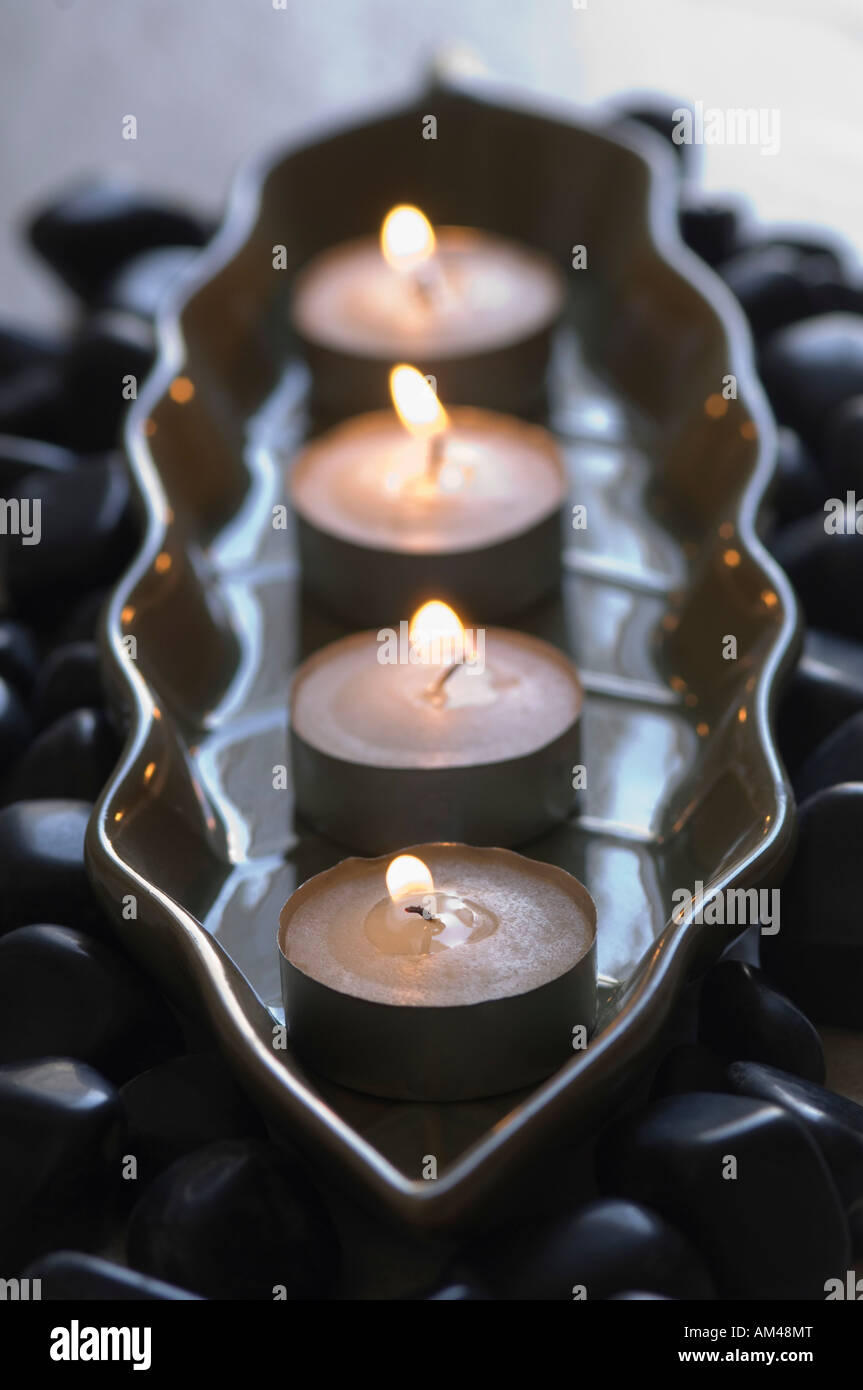 Close-up of four aromatherapy candles burning in a tray with black pebbles - Stock Image