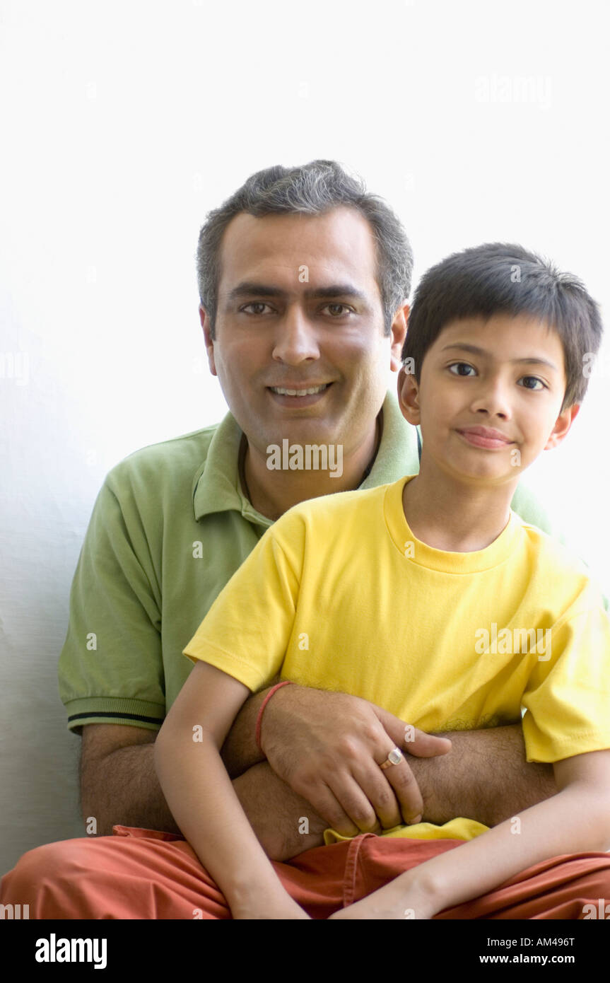 Portrait of a boy sitting with his father - Stock Image