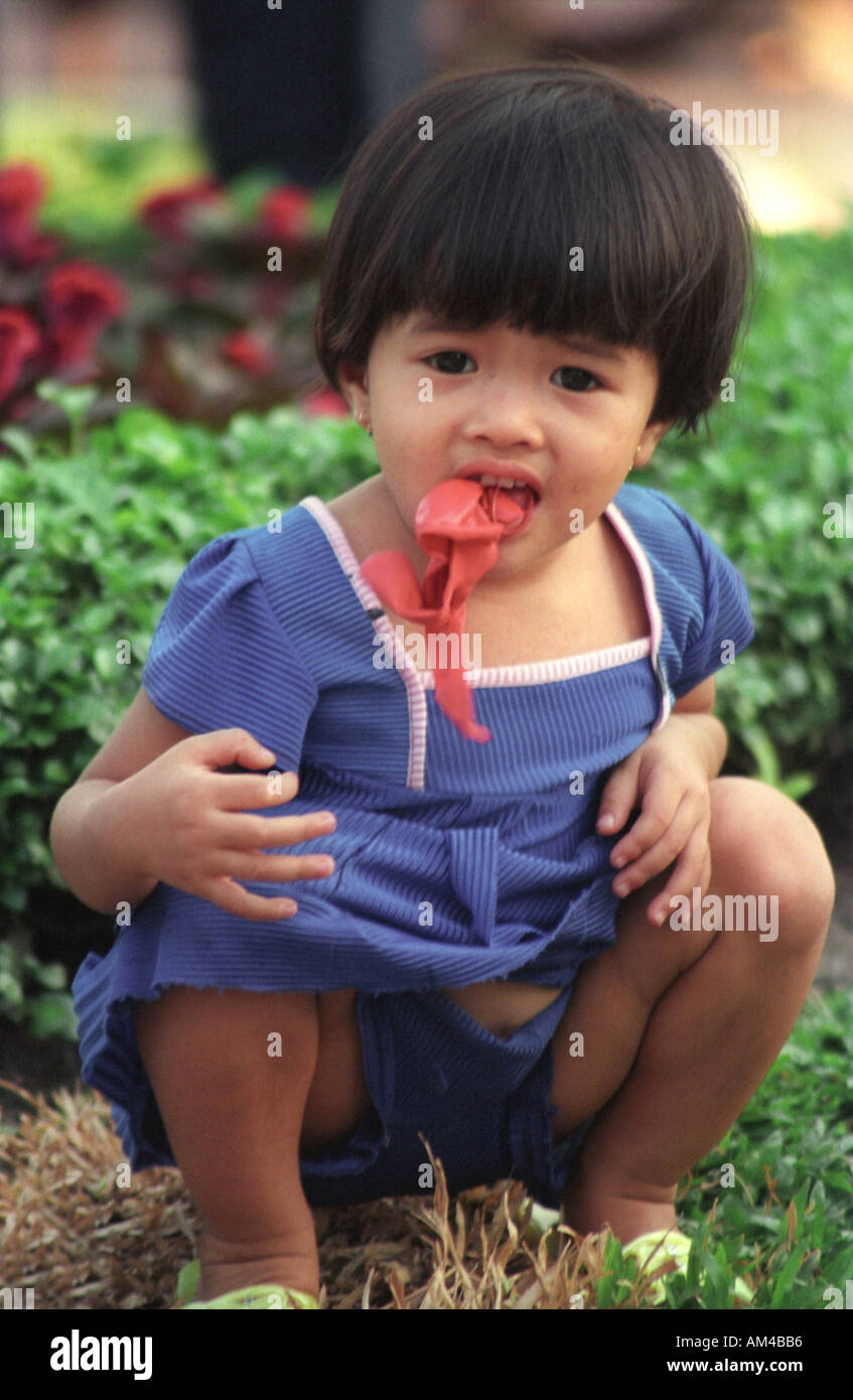 Young Vietnamese girl plays with a small balloon in Ho Chi Minh City Vietnam Stock Photo