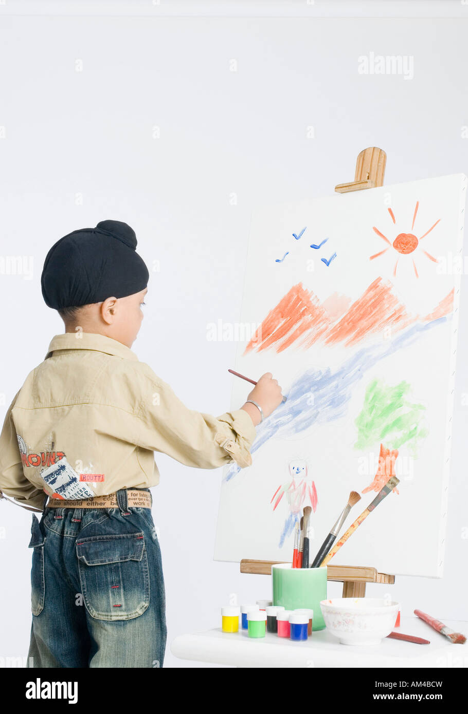 Rear view of a boy painting on an artist's canvas - Stock Image