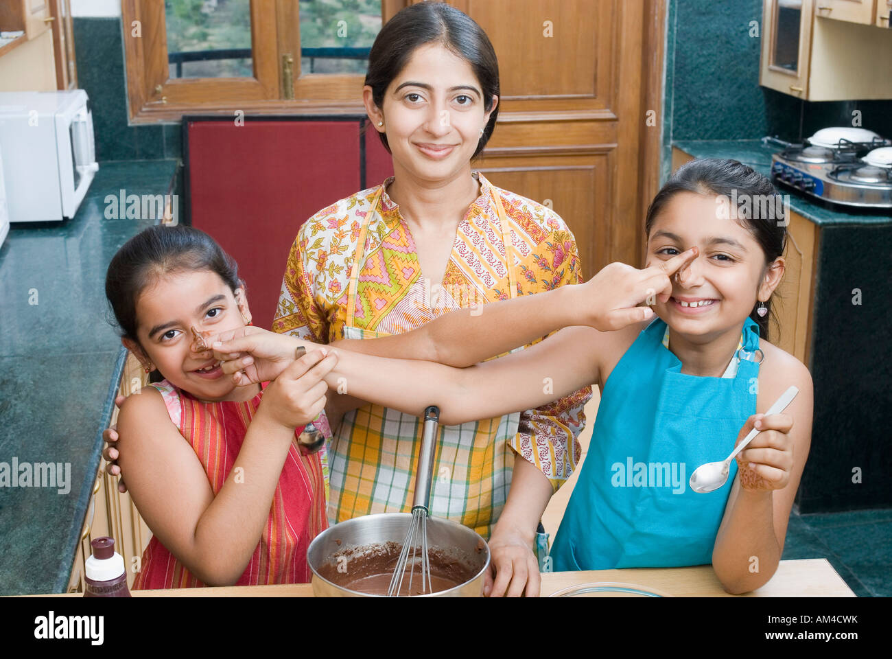 Portrait of a mid adult woman baking chocolate sauce with her daughters touching each other's nose - Stock Image