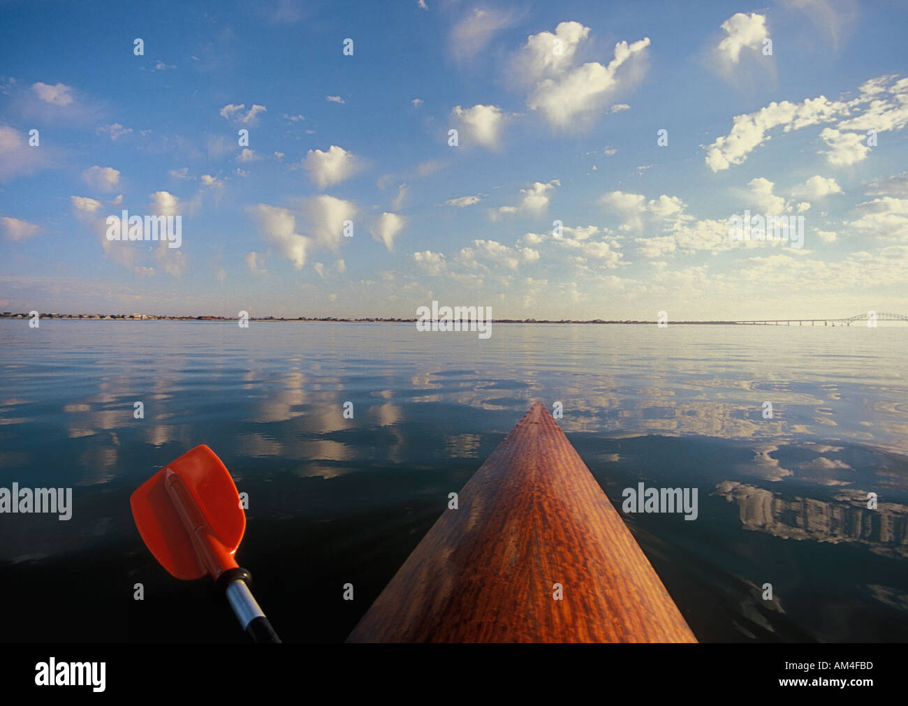 looking over the bow of a wooden kayak resting on a glassy smooth sea. - Stock Image