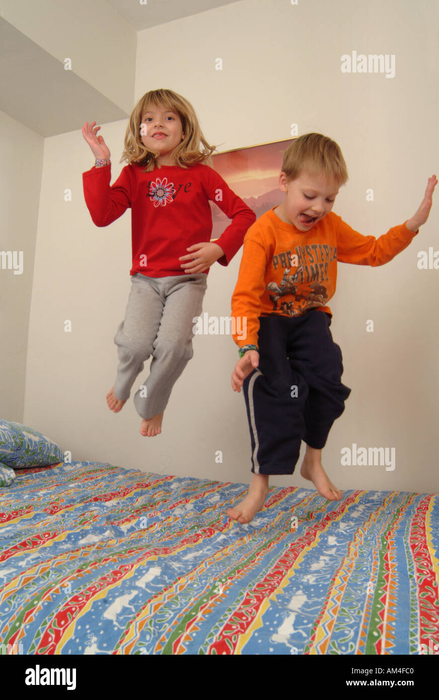 a boy and a girl jumping on a bed Stock Photo