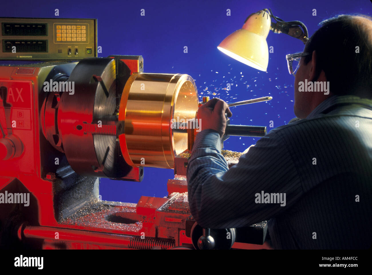 machine shop worker cuts into brass on a metal lathe - Stock Image