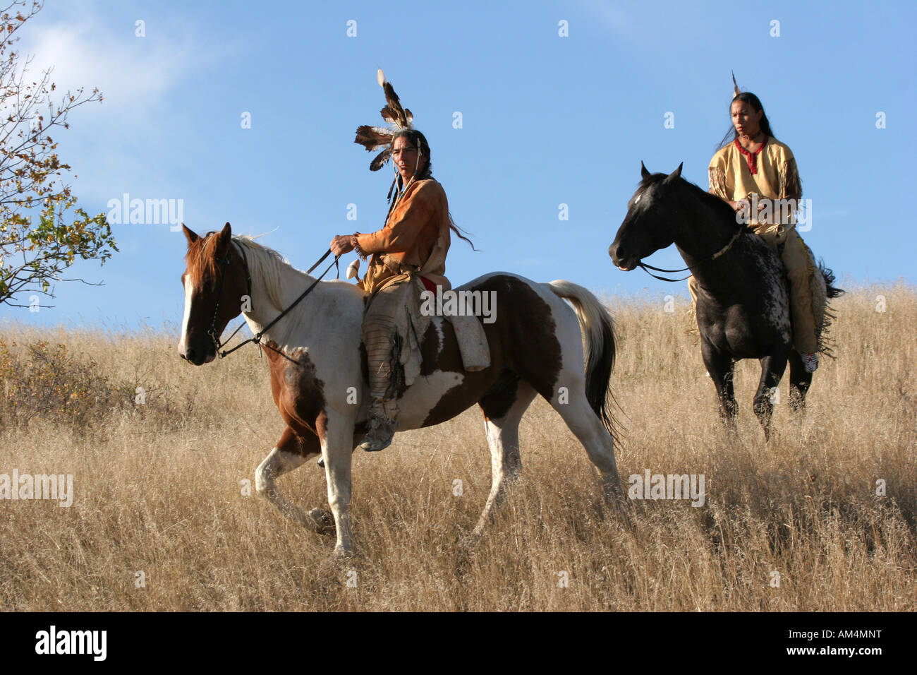 Two Native American Indian men on horseback scouting for enemies or hunting for food in the prairie of South Dakota - Stock Image