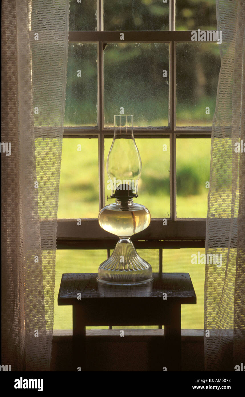 A clear glass oil lamp in home window with lace curtains. - Stock Image