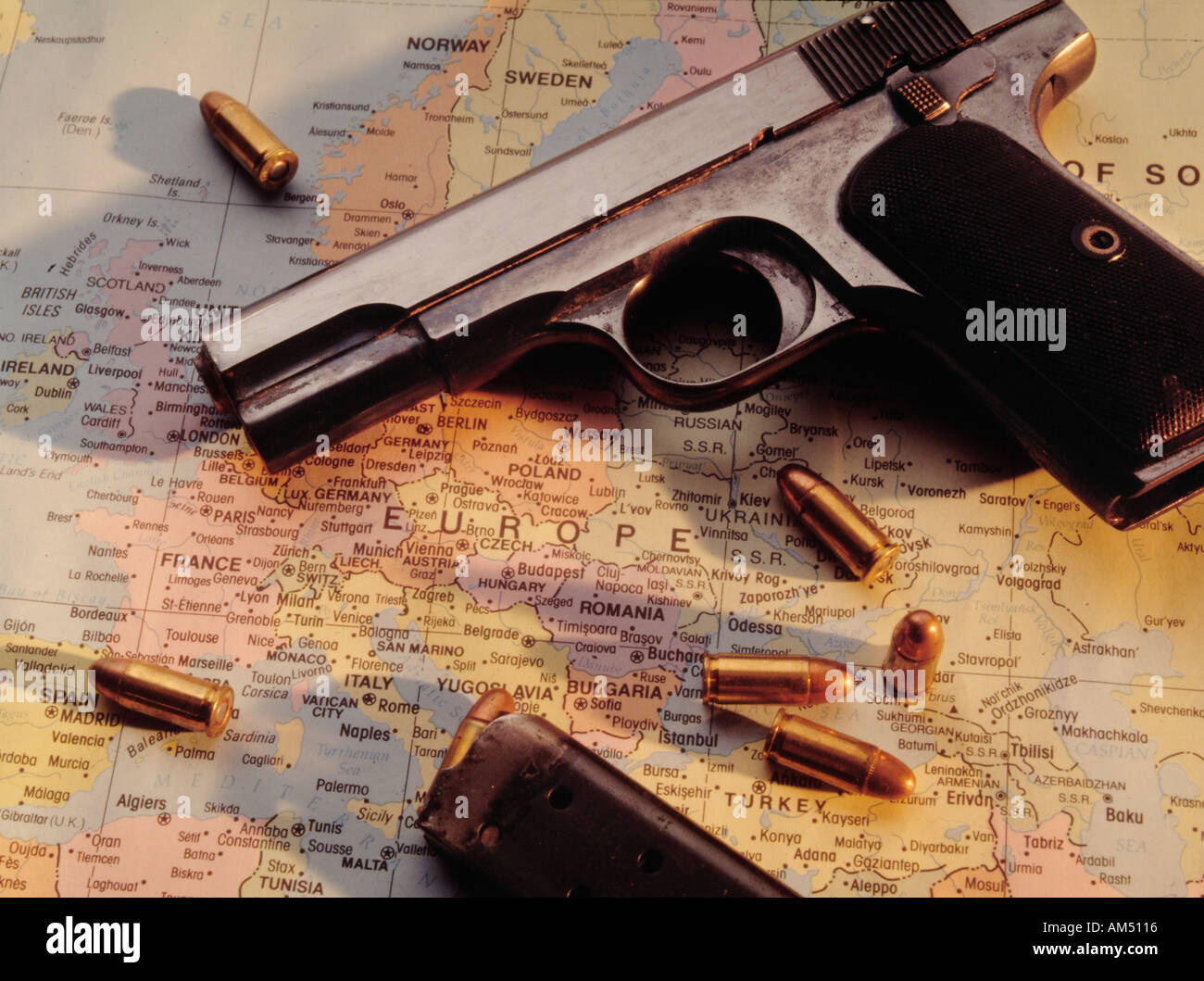 Automatic pistol and bullets on map of Europe - Stock Image