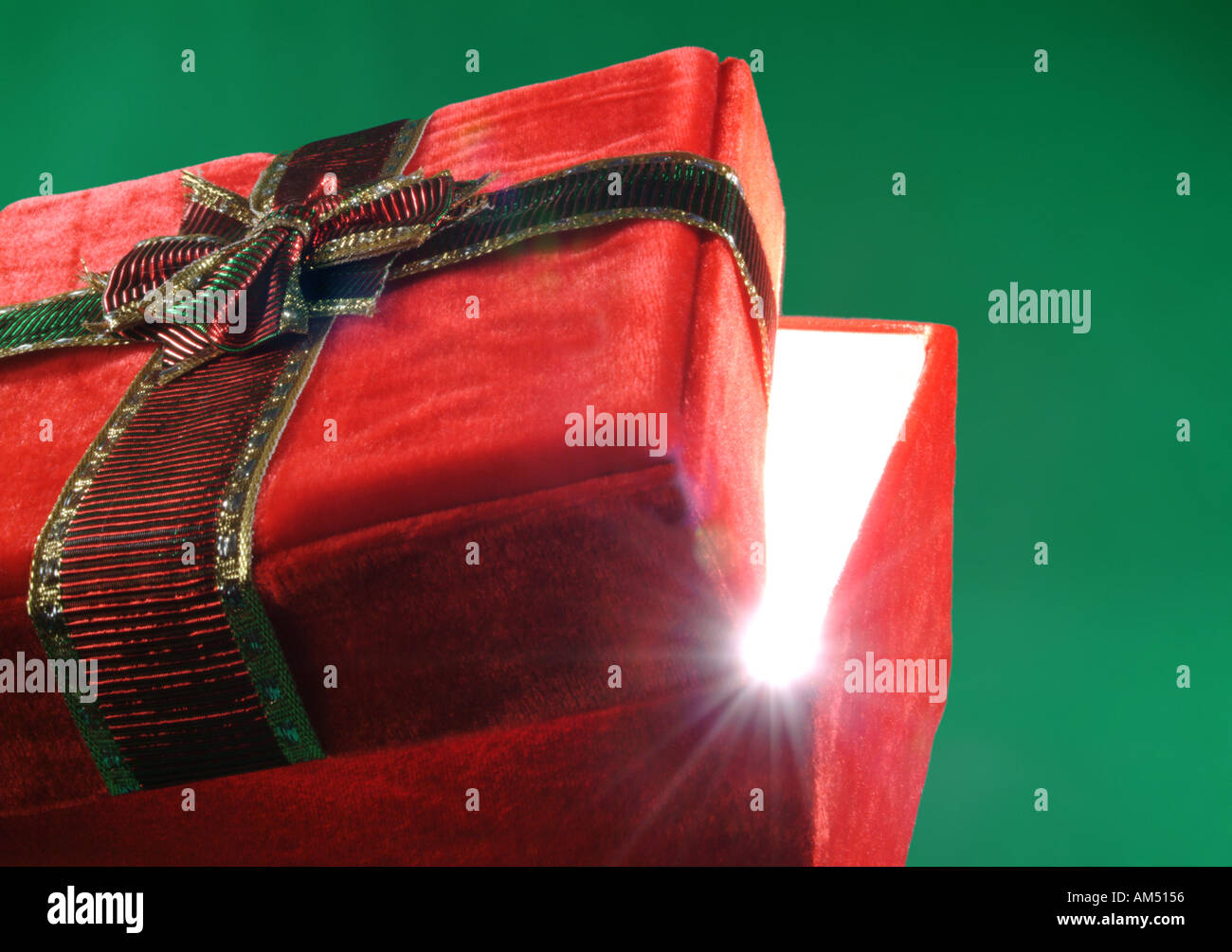 red gift box with lid ajar and rays of light bursting out - Stock Image