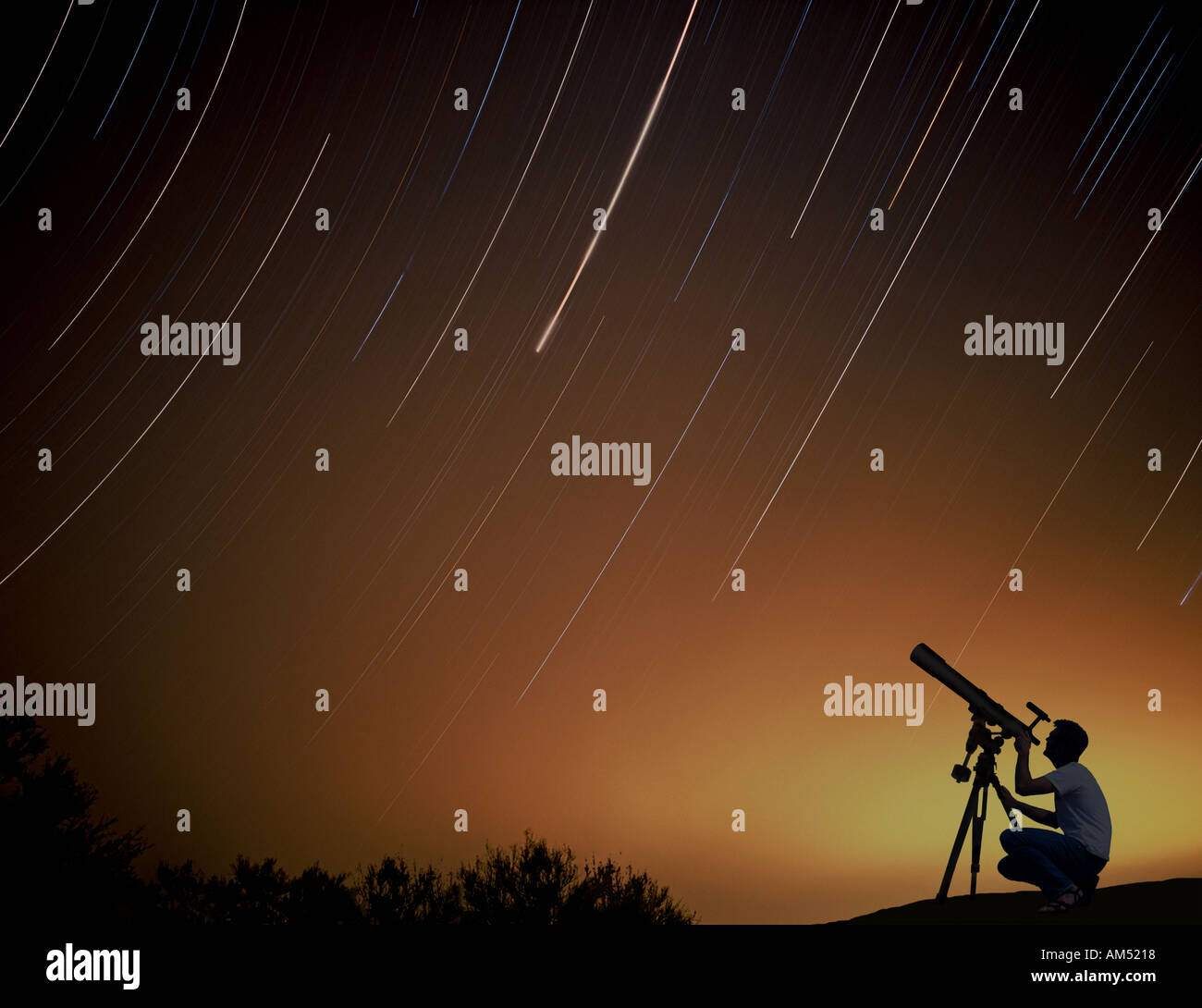 A man with a telescope looks at the night sky. Star trails in the night sky made during a long exposure. - Stock Image