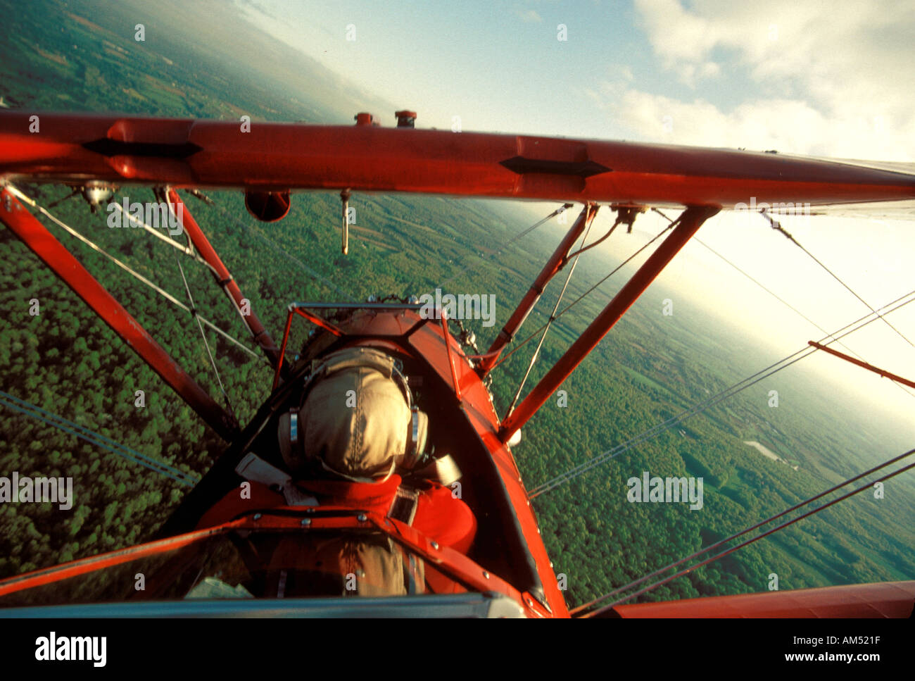 red open cockpit bi plane in a steep turn - Stock Image