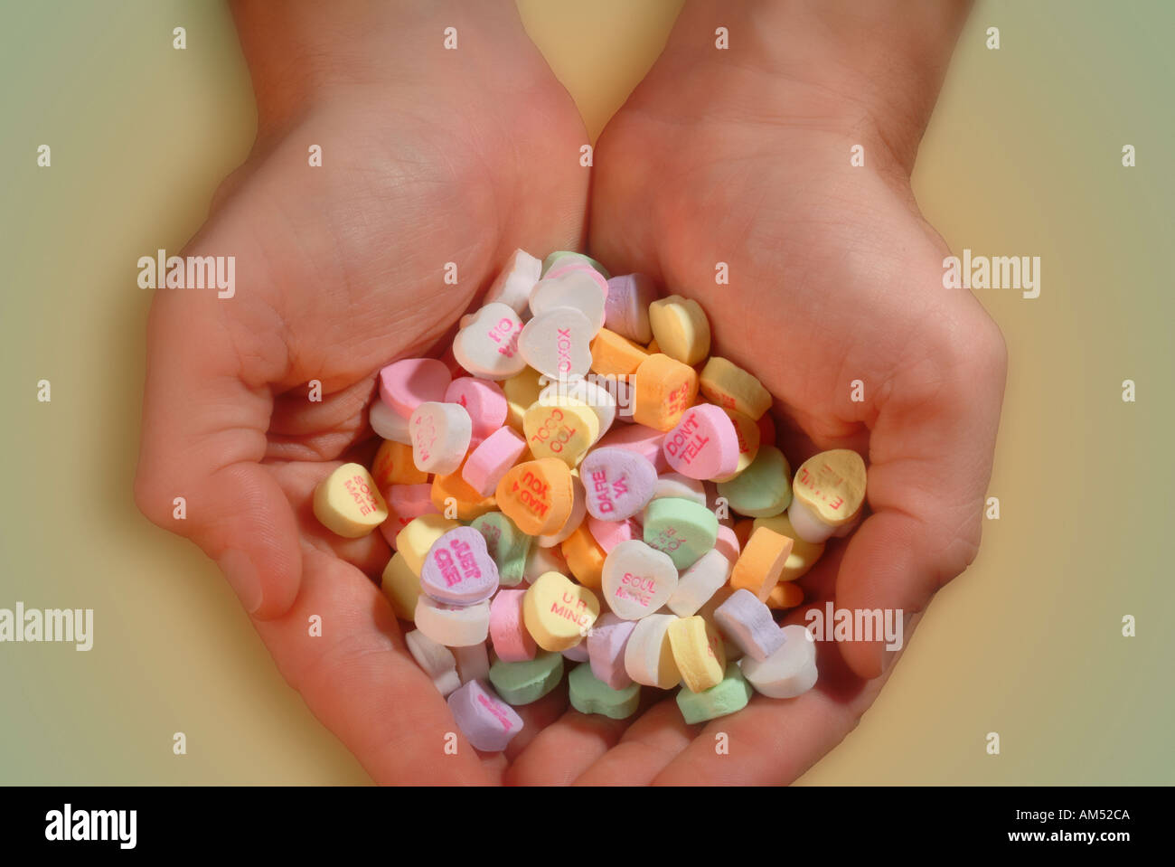 handful of heart shaped Valentine candy - Stock Image