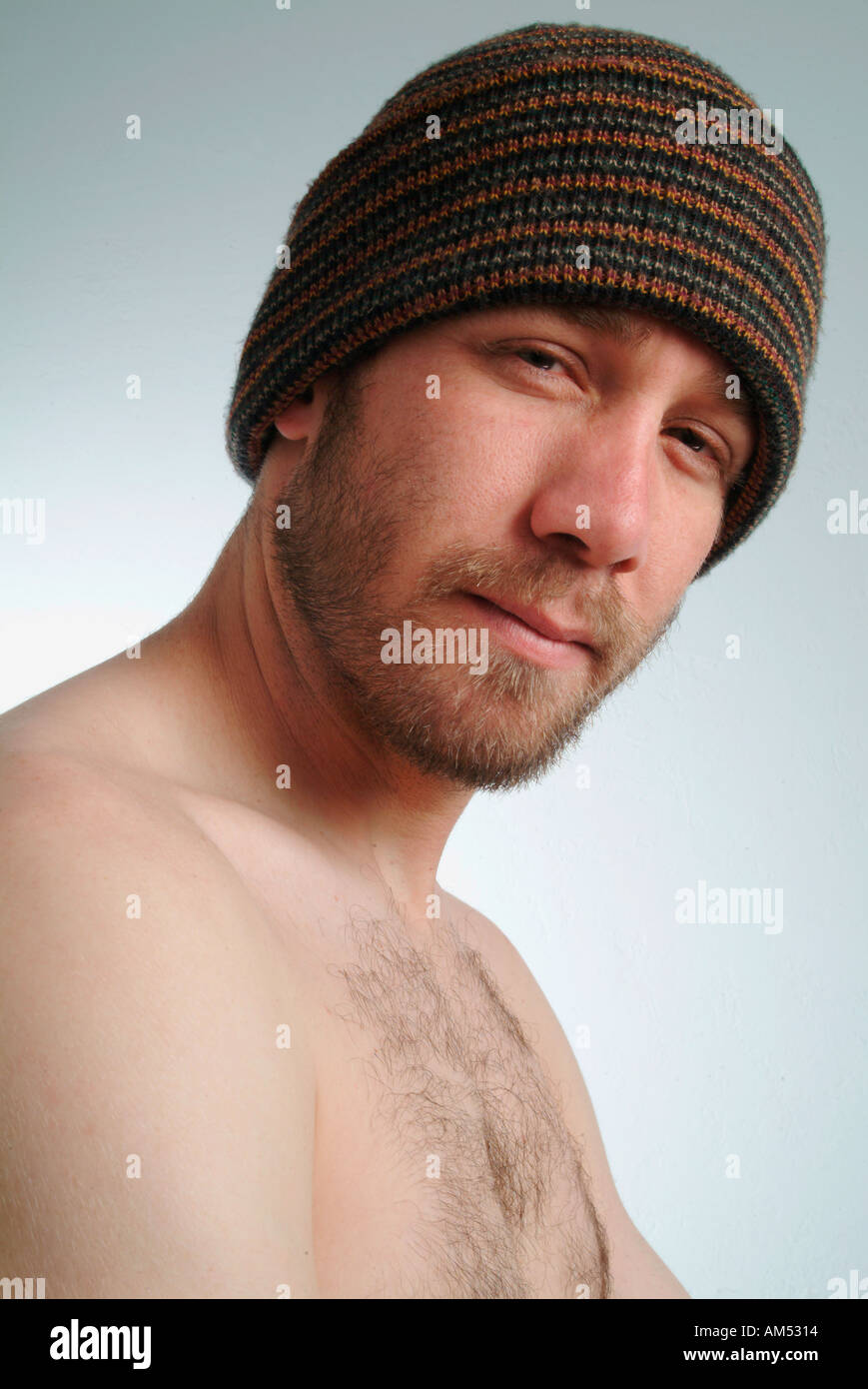 Glaring young 20 something man with beard and ski hat and no shirt - Stock Image