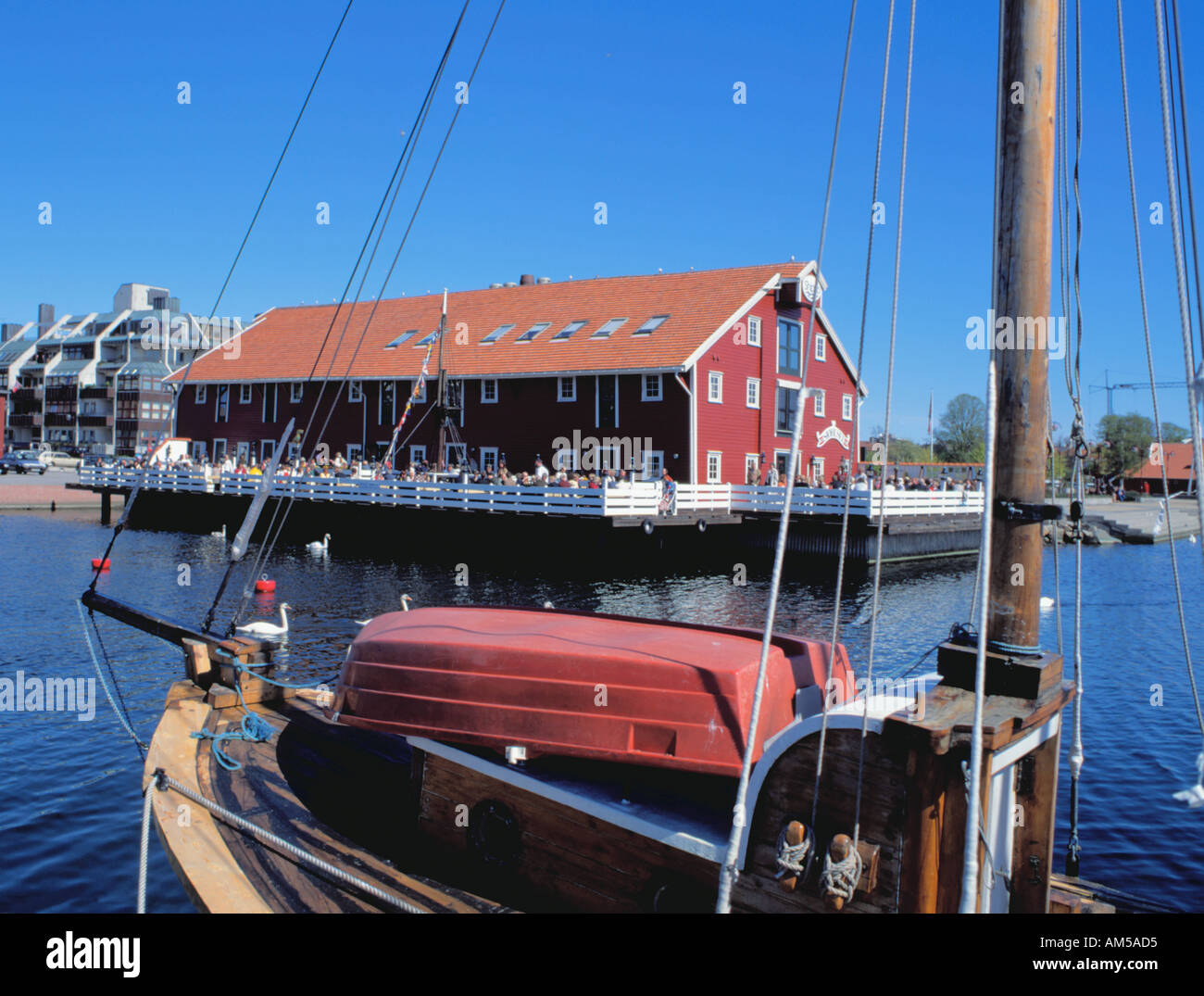 Picturesque converted old timber warehouse (now a cafe restaurant) seen over the harbour, Kristiansand, Vest-Agder, Norway. - Stock Image