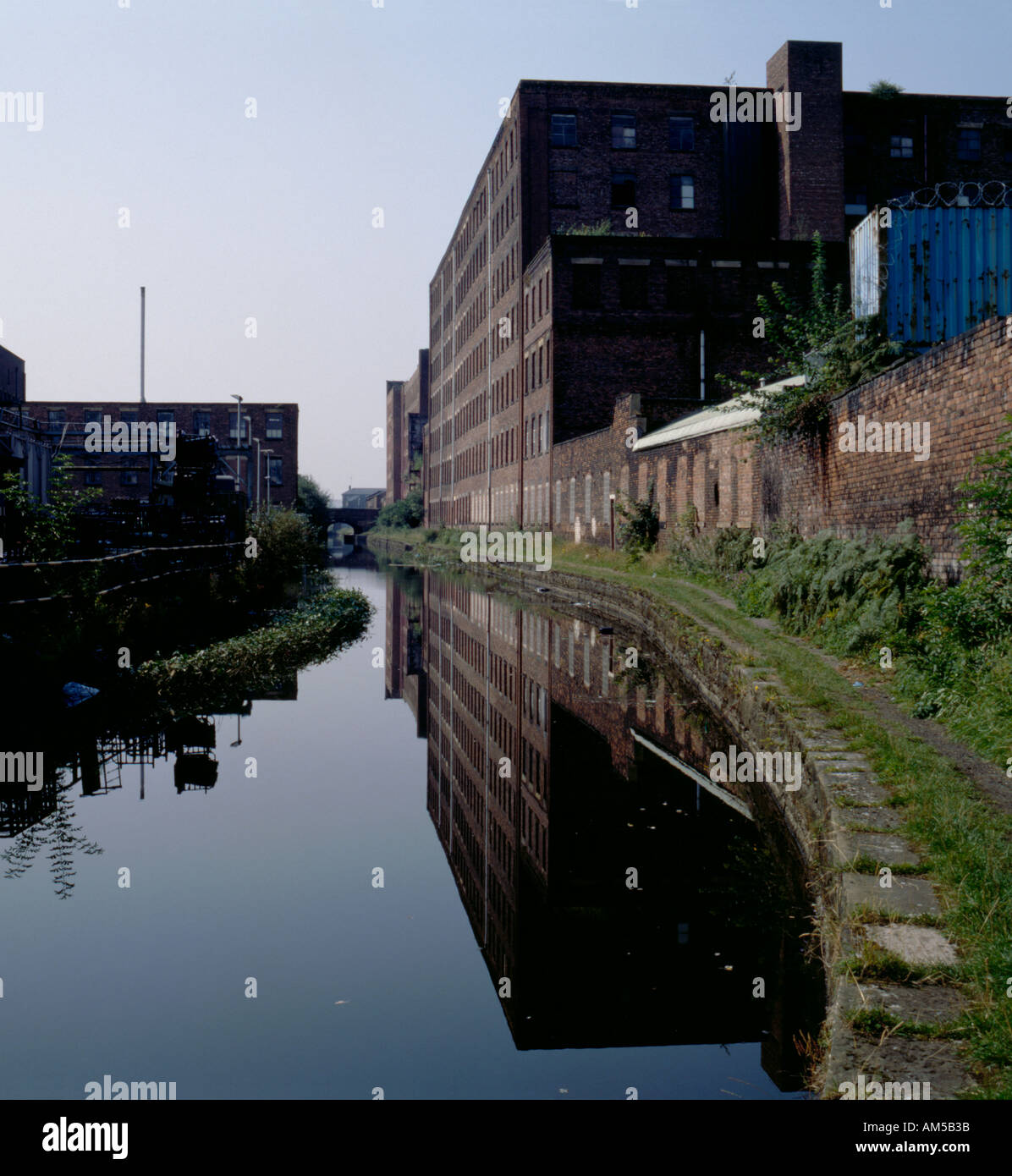 Old mill beside the Ashton under Lyne Canal, Holt Town area, Greater Manchester, England, UK. - Stock Image