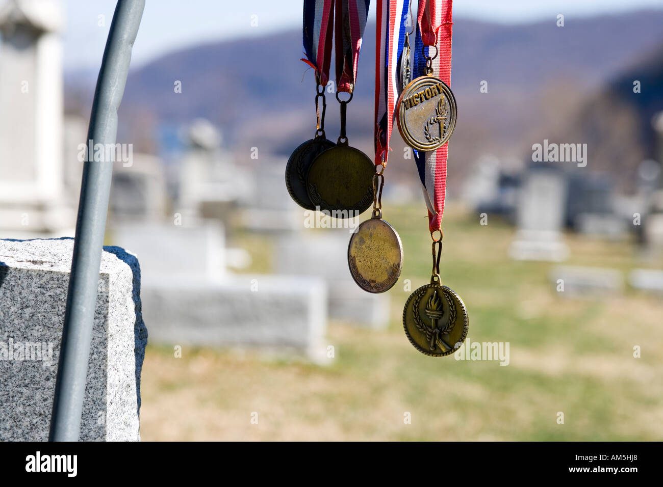 Victory medals hanging from a tombstone at the cemetery of Harpers Ferry West Virginia USA - Stock Image