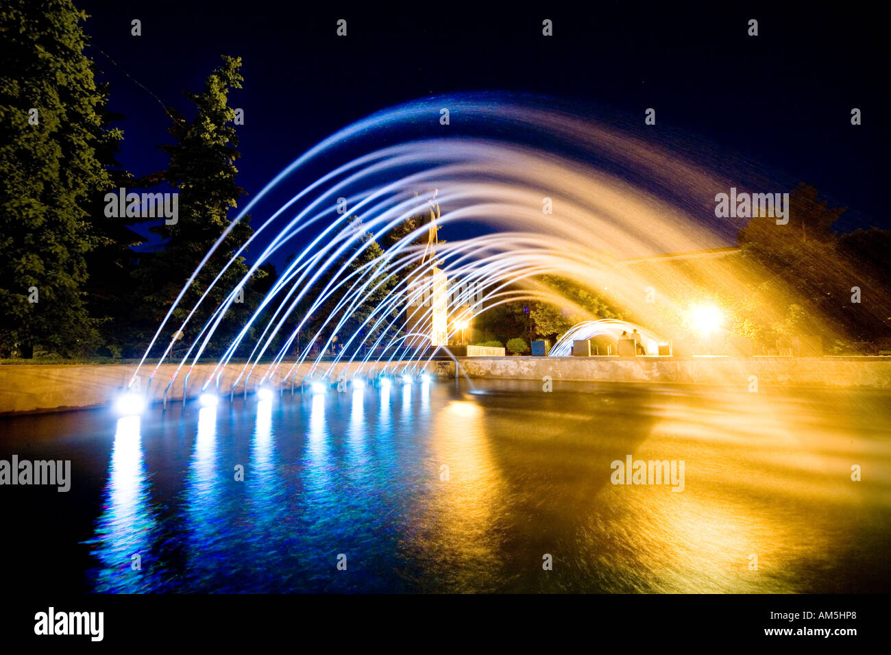 Colorful illuminated fountain of the monument to Chokan Valikhanov in central Almaty, Kazakhstan by night. - Stock Image