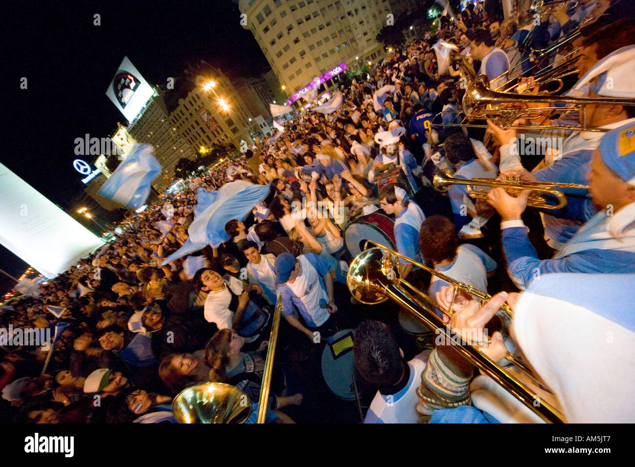Musicians play trombone and trumpets to a cheering and dancing crowd of soccer fans underneath the Obelisk in Buenos Aires. - Stock Image