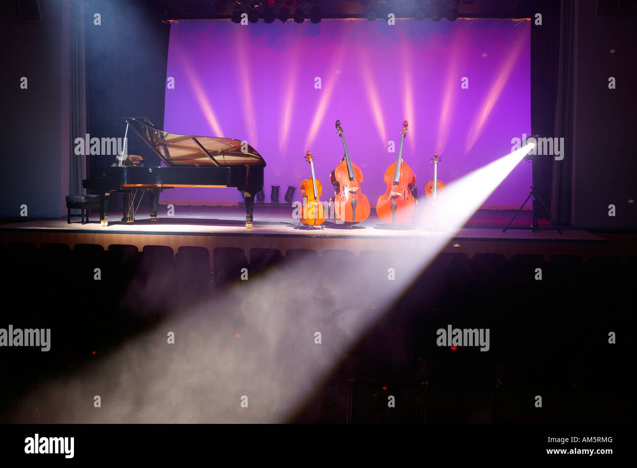 Stringed instruments and piano on stage, fog and spots - Stock Image
