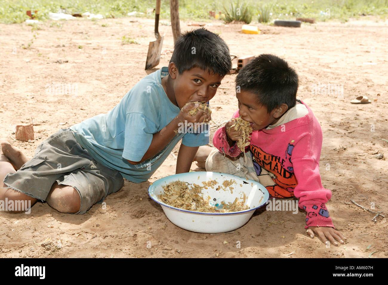 Children eating fresh, hackled sugar cane, Nivaclé native American, Jothoisha, Chaco, Paraguay, South America - Stock Image