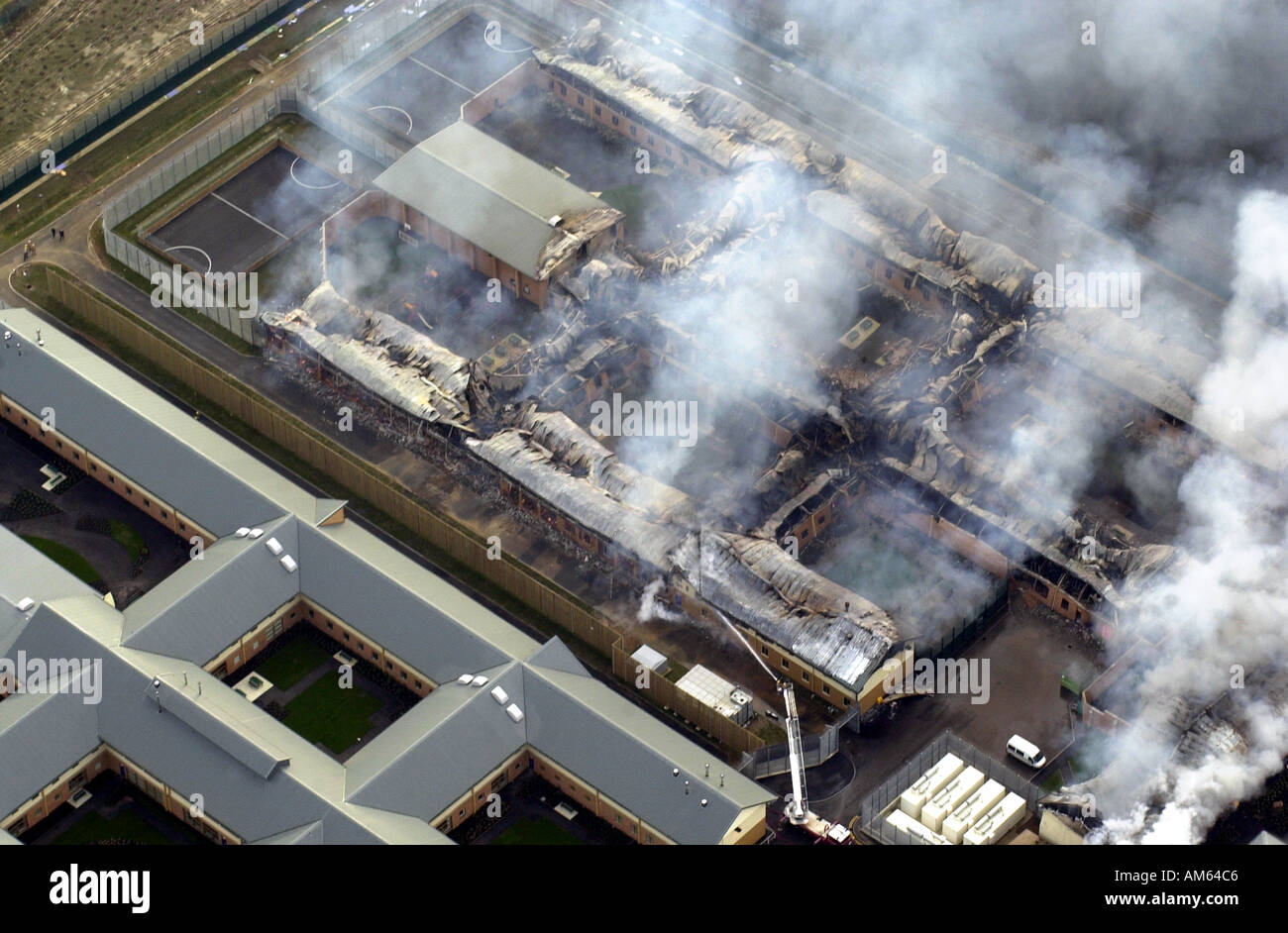 Yarlswood detention centre fire Aerial view of the damge caused showing fire crews still at work the next morning UK - Stock Image