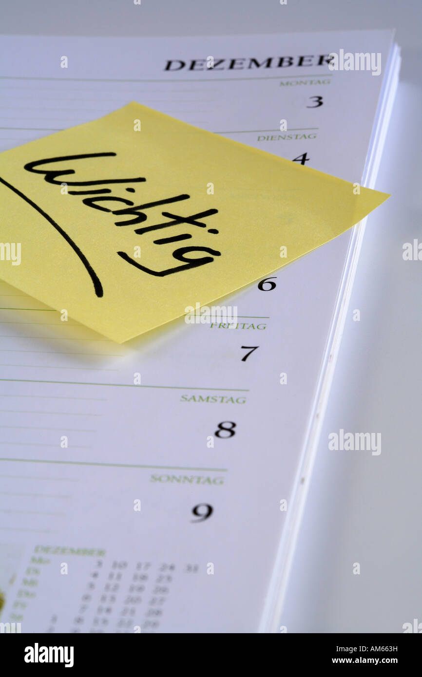 Yellow reminder note 'Wichtig' (important) on the page of a calendar - Stock Image