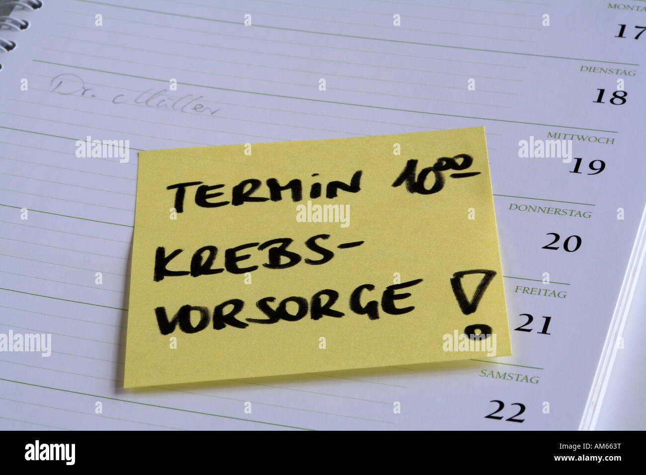 Yellow reminder note 'Termin' (cancer checkup appointment) on the page of a calendar - Stock Image