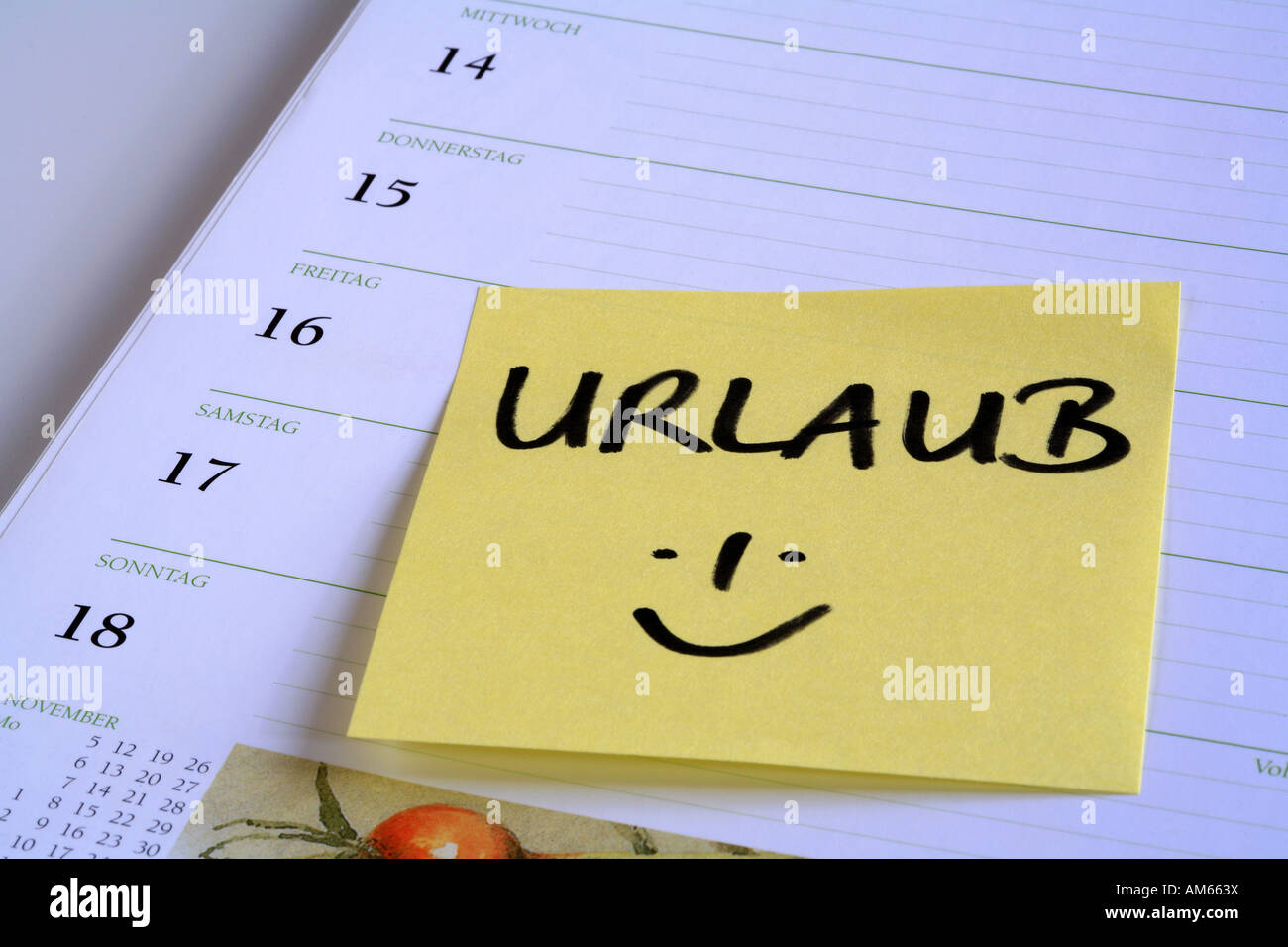 Yellow reminder note 'Urlaub' (holiday) on the page of a calendar - Stock Image