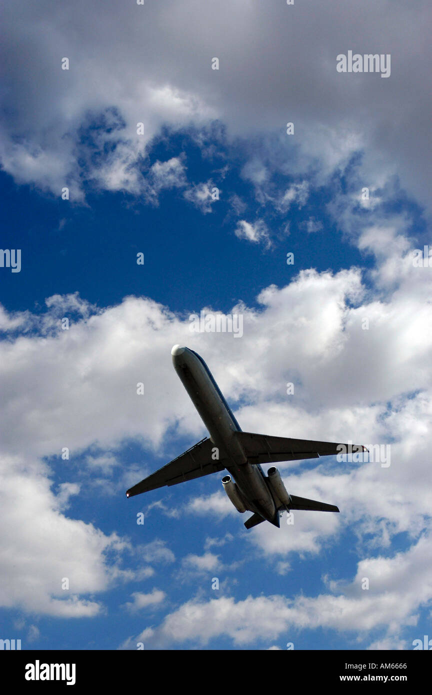 commercial airliner highlighted against clouds and blue sky - Stock Image