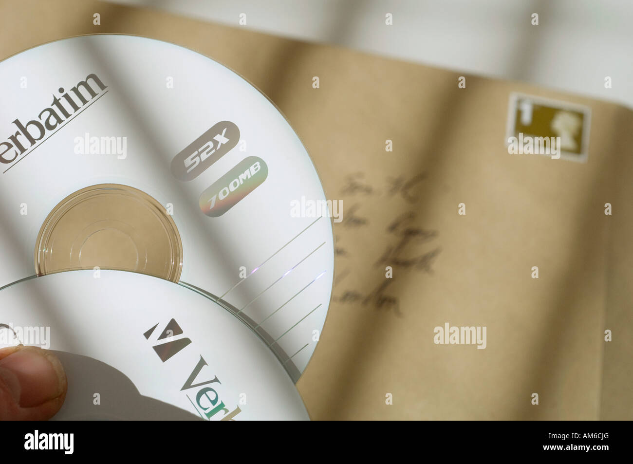 Two computer data discs being put in an envelope. Picture by Jim Holden. Stock Photo