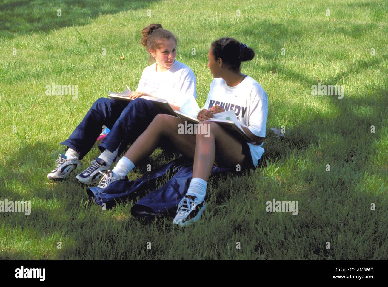 Friends age 14 studying together on grass. Minnetonka Minnesota USA Stock Photo
