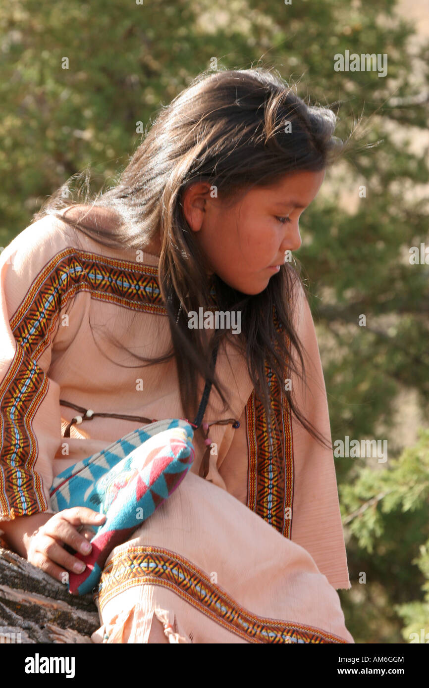 A young Native American Indian girl sitting in a tree playing - Stock Image