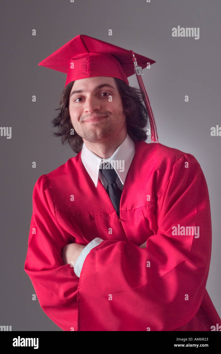 Happy male graduate in red cap and gown with arms crossed Stock ...