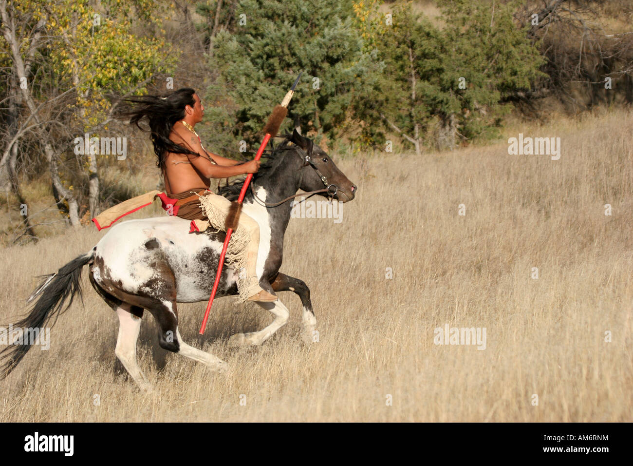 A Native American Indian man riding bareback on a horse in ...