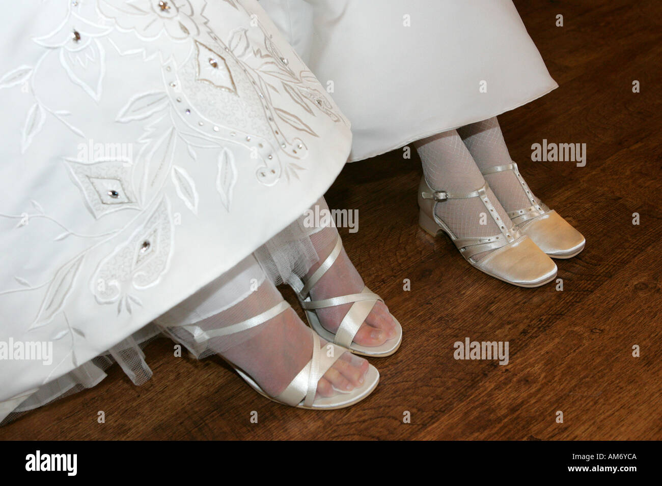 Closeup Of A Brides White Wedding Shoes And Dress And Her