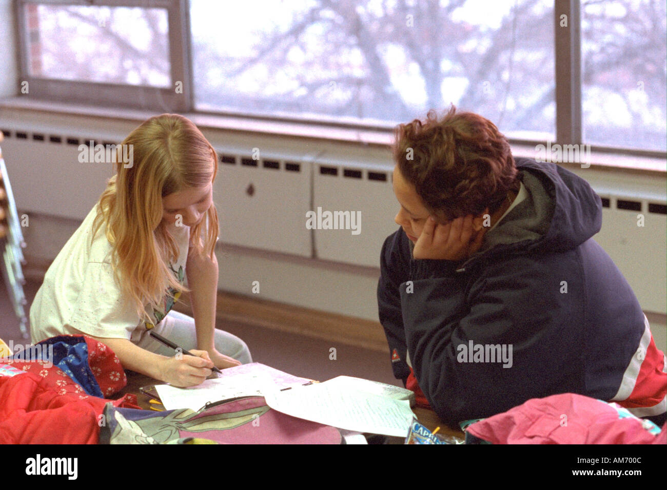 Mentor and child studying in after school reading program age 18 and 9. St Paul Minnesota USA Stock Photo