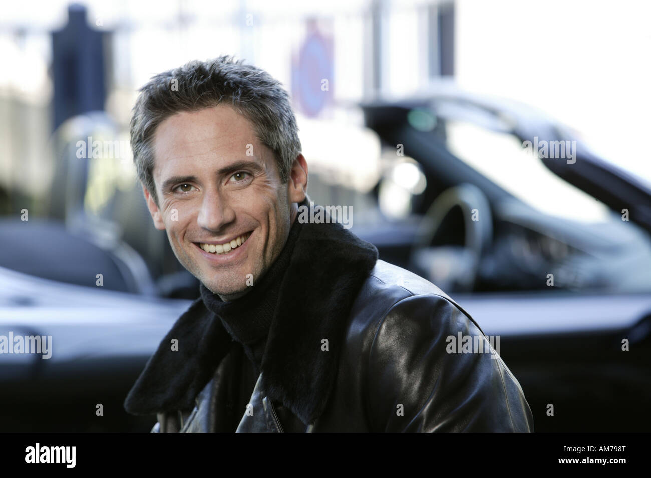Man in leather jacket in front of his sports car - Stock Image