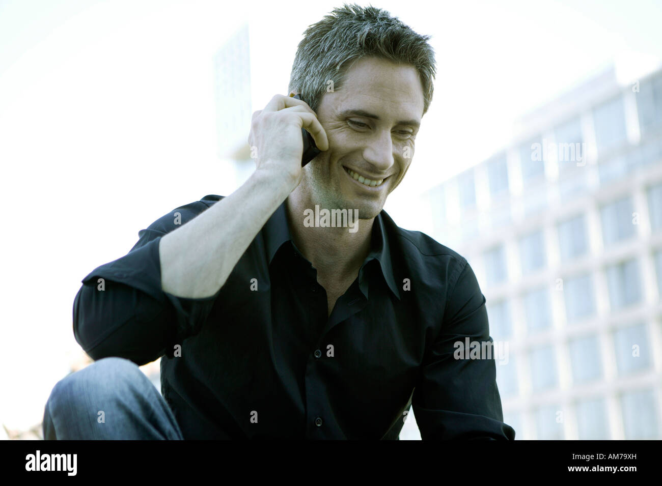 Man in black shirt talking on his mobile - Stock Image