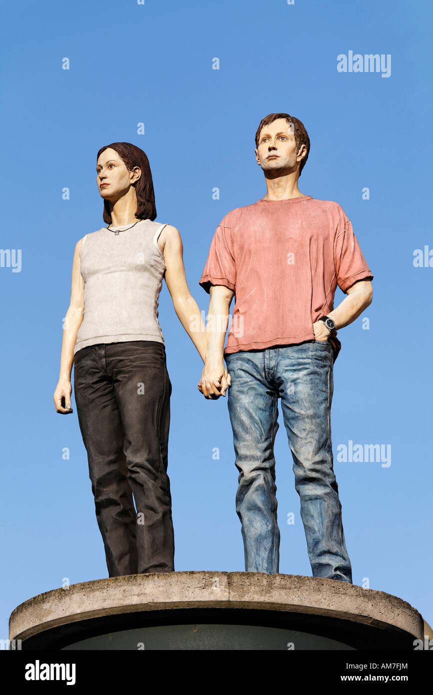 Young couple holding hands, sculpture standing at the top of a advertising column, Duesseldorf, NRW, Germany Stock Photo