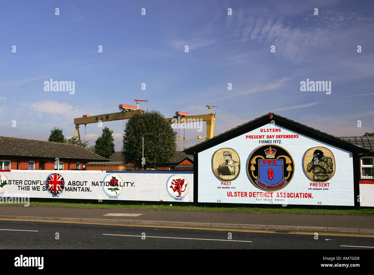 Bright wall painted Ulster Defence Association murals on Newtownards Road with famous yellow Harland and Wolff cranes Stock Photo