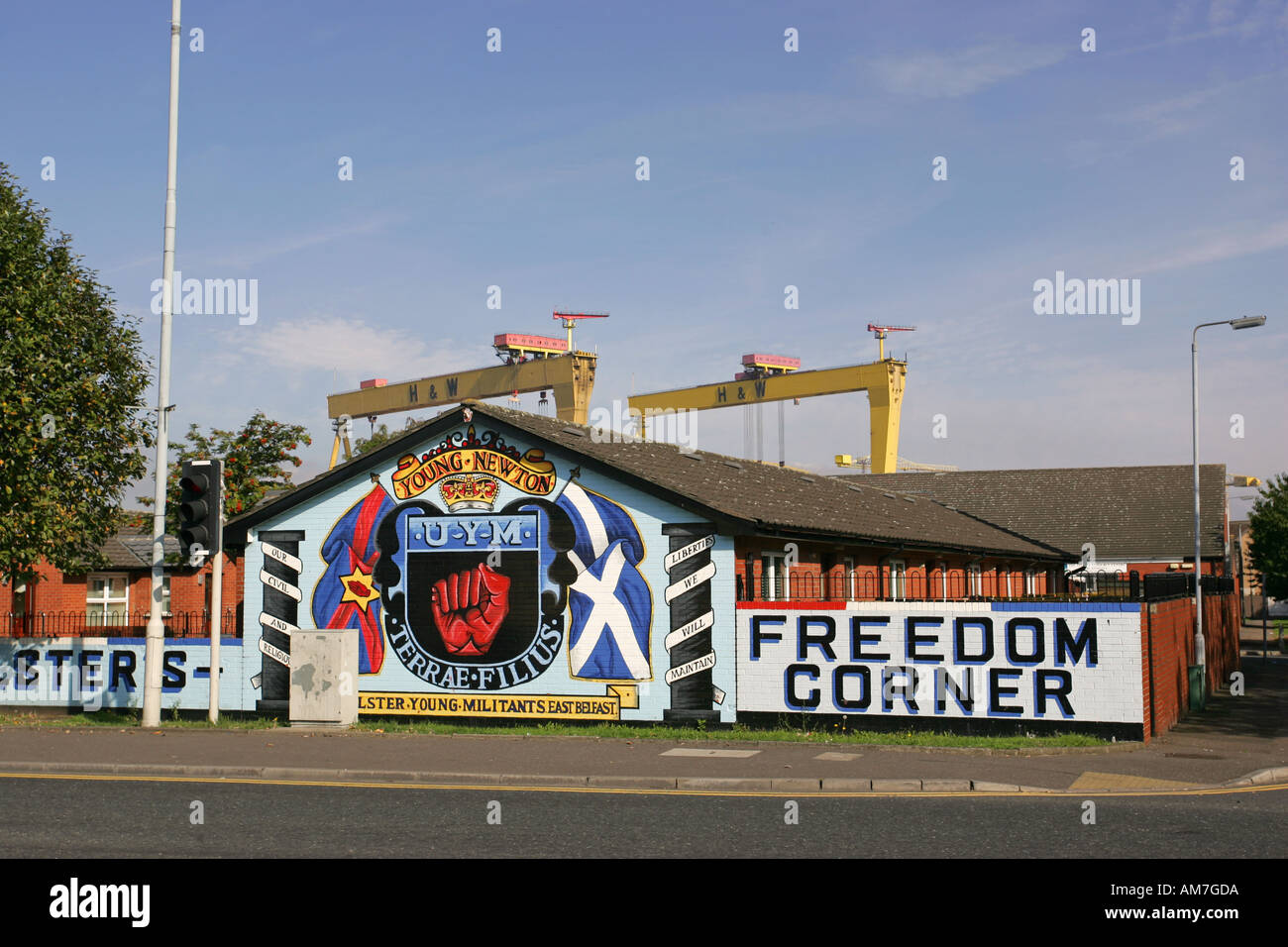 Bright wall painted Ulster Defence Association murals on Newtownards Road with famous yellow Harland and Wolff cranes Belfast NI - Stock Image