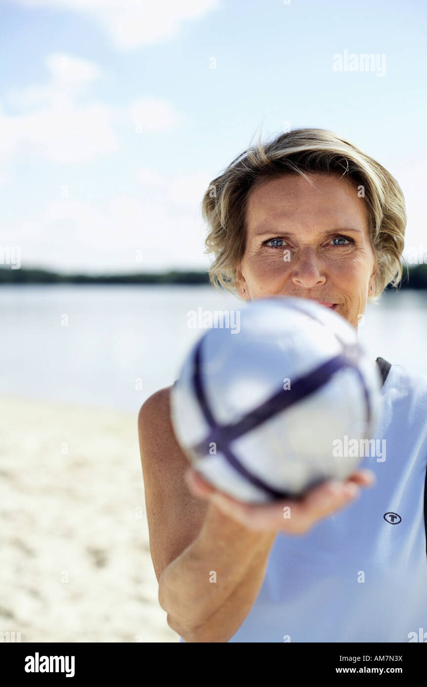 Bestager 60+ with volleyball on the beach - Stock Image