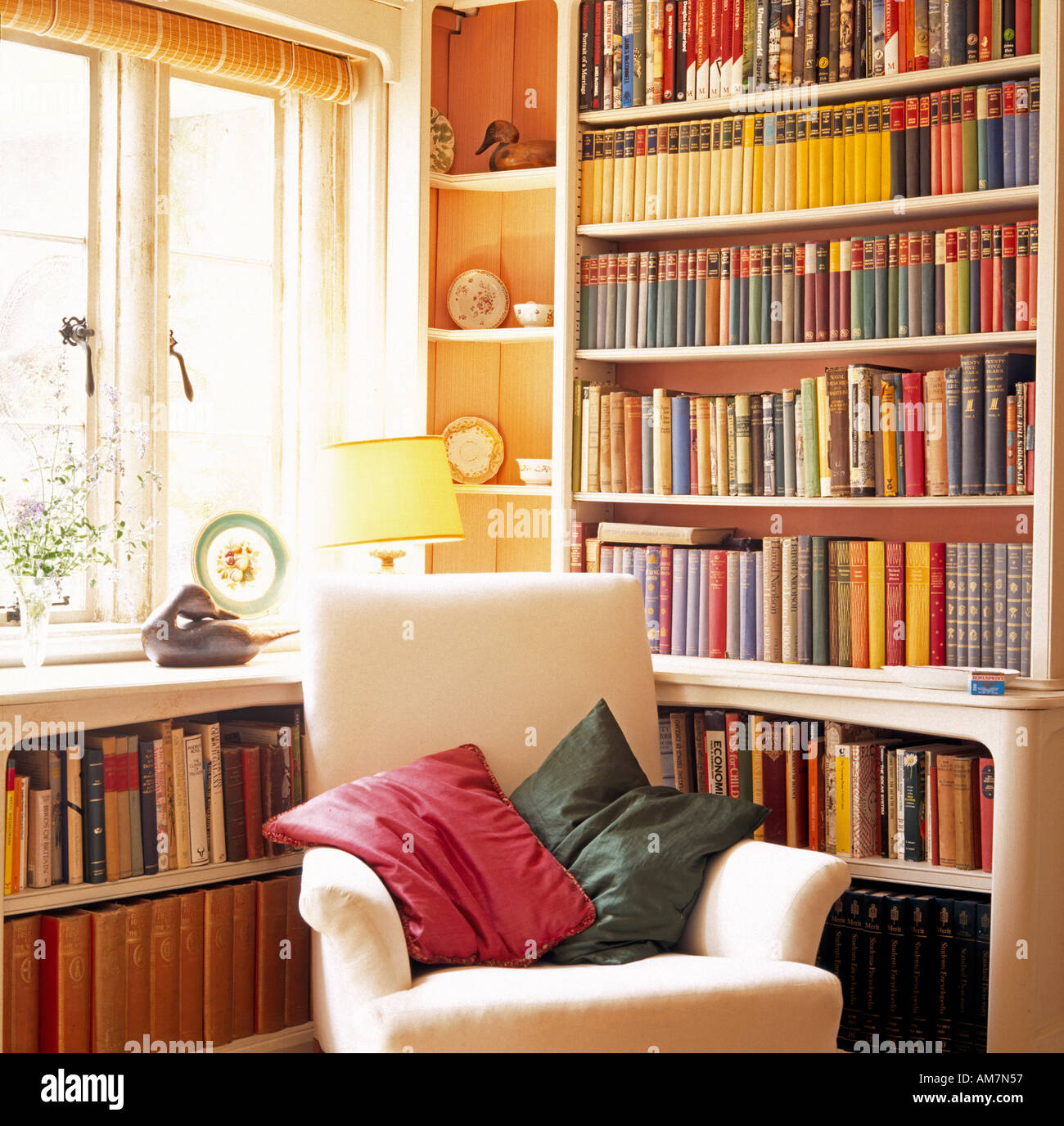 Armchair with bookcase in sitting room of Phyllis Cottage country house Wiltshire England - Stock Image