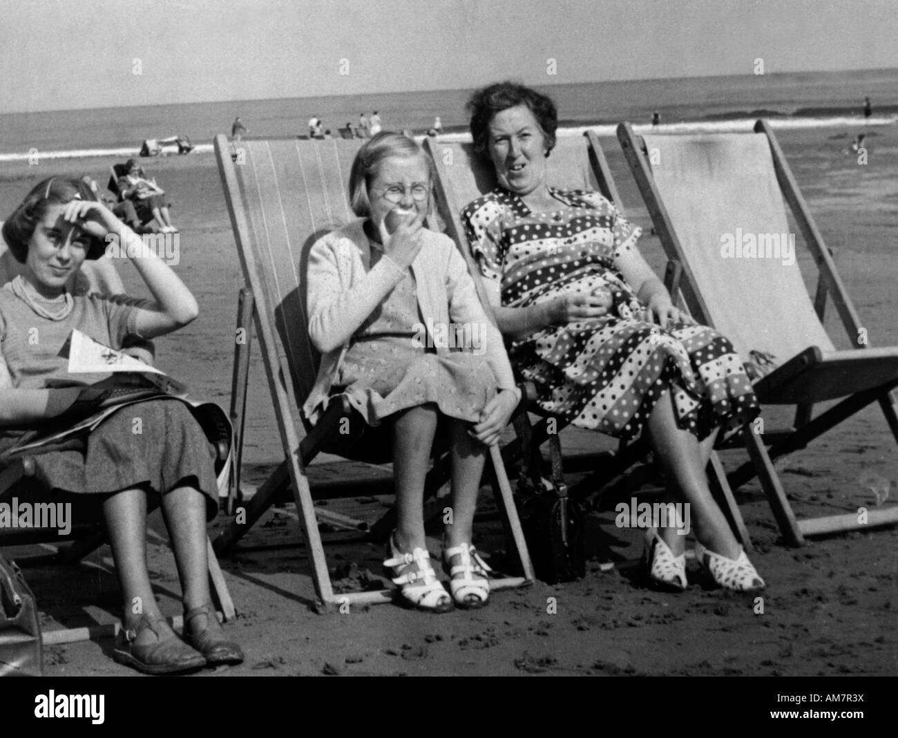 Old vintage family snapshot photograph of mother and two daughters sitting in deck chairs on beach