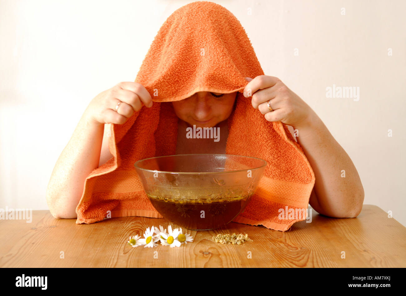 Woman inhaling over glass bowl Stock Photo
