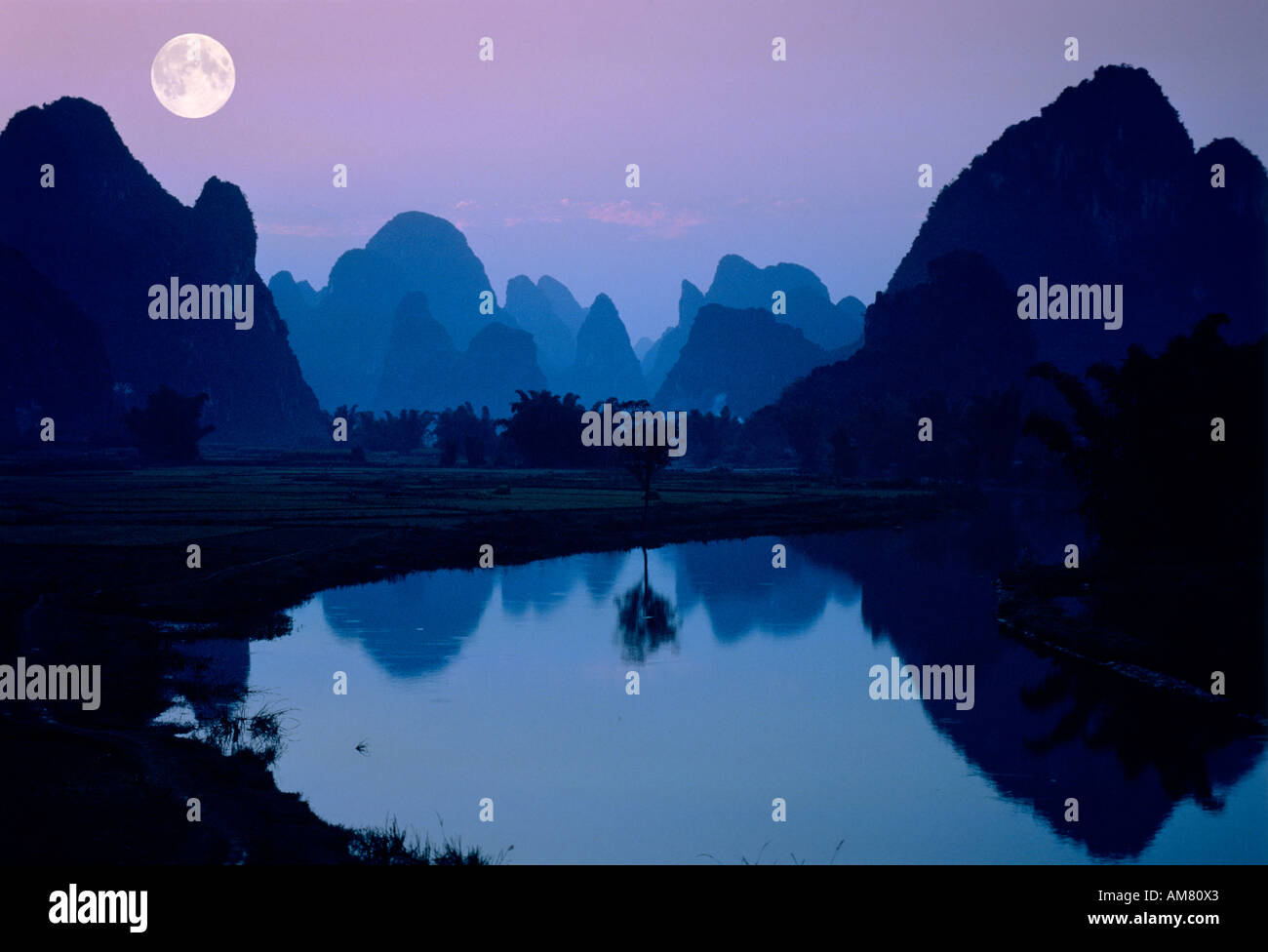 Lake with fullmoon and Mountains at night - Stock Image