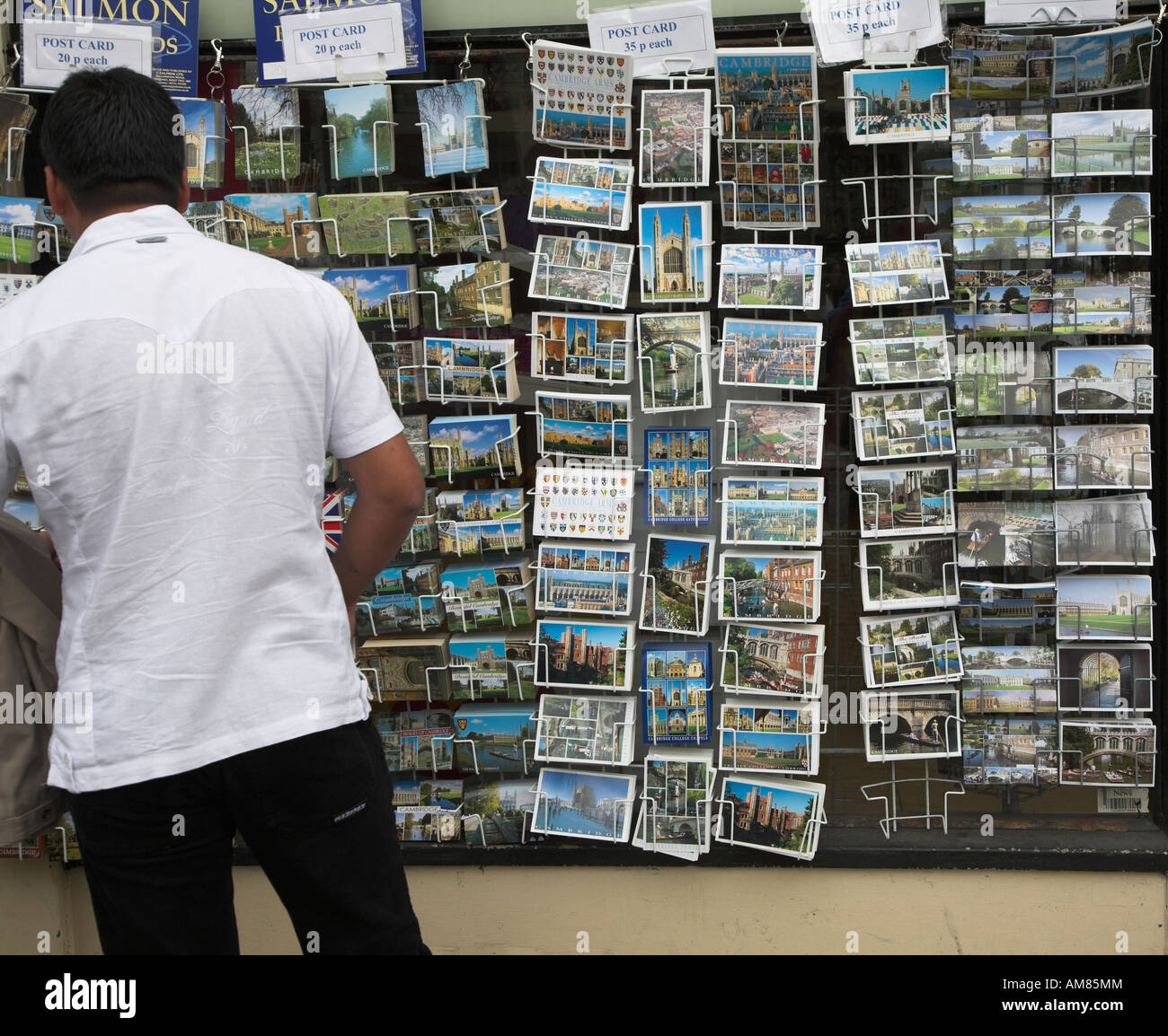 Man looking through postcards on display Cambridge England - Stock Image