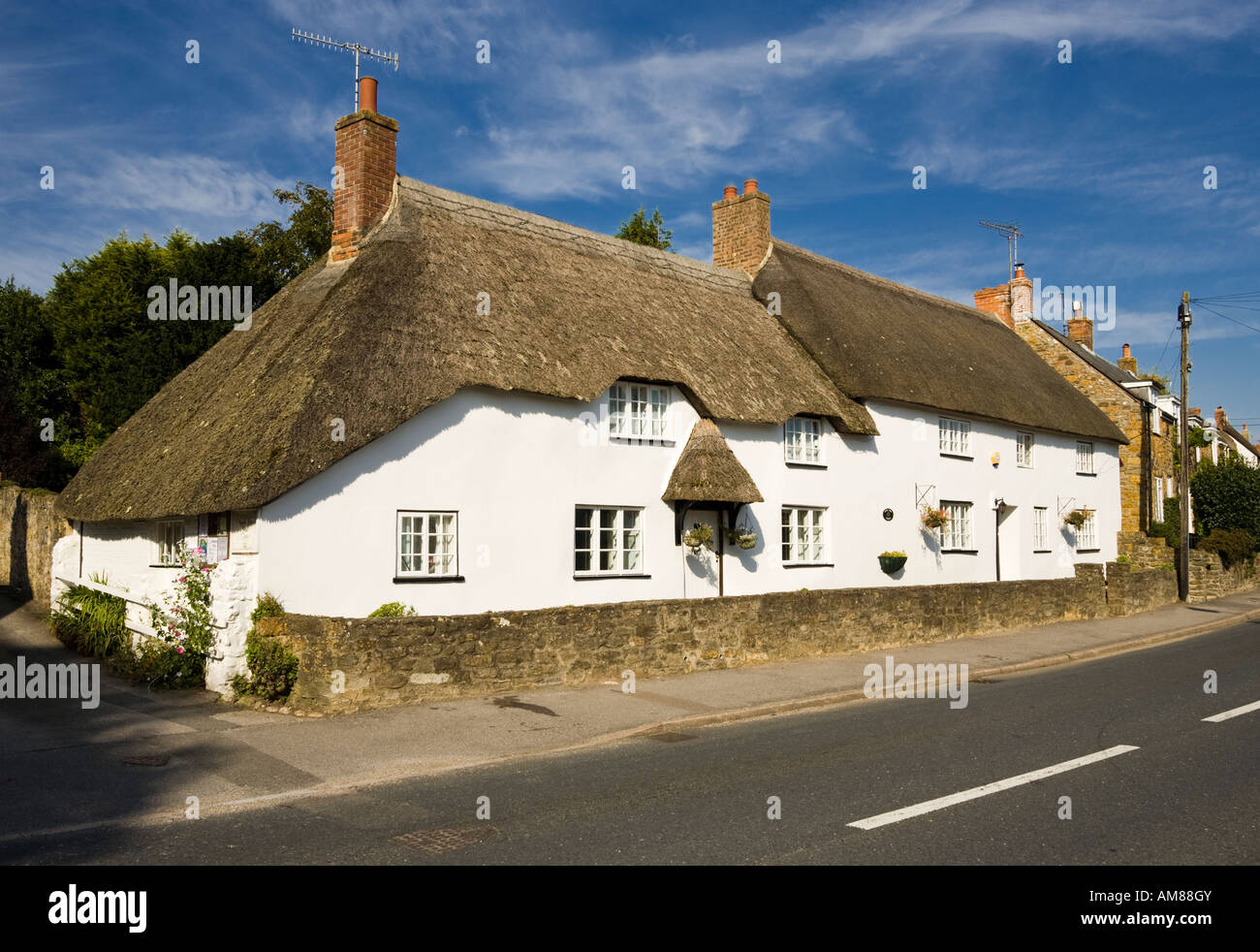 Thatched cottages in village of Chideock, Dorset, England, UK - Stock Image