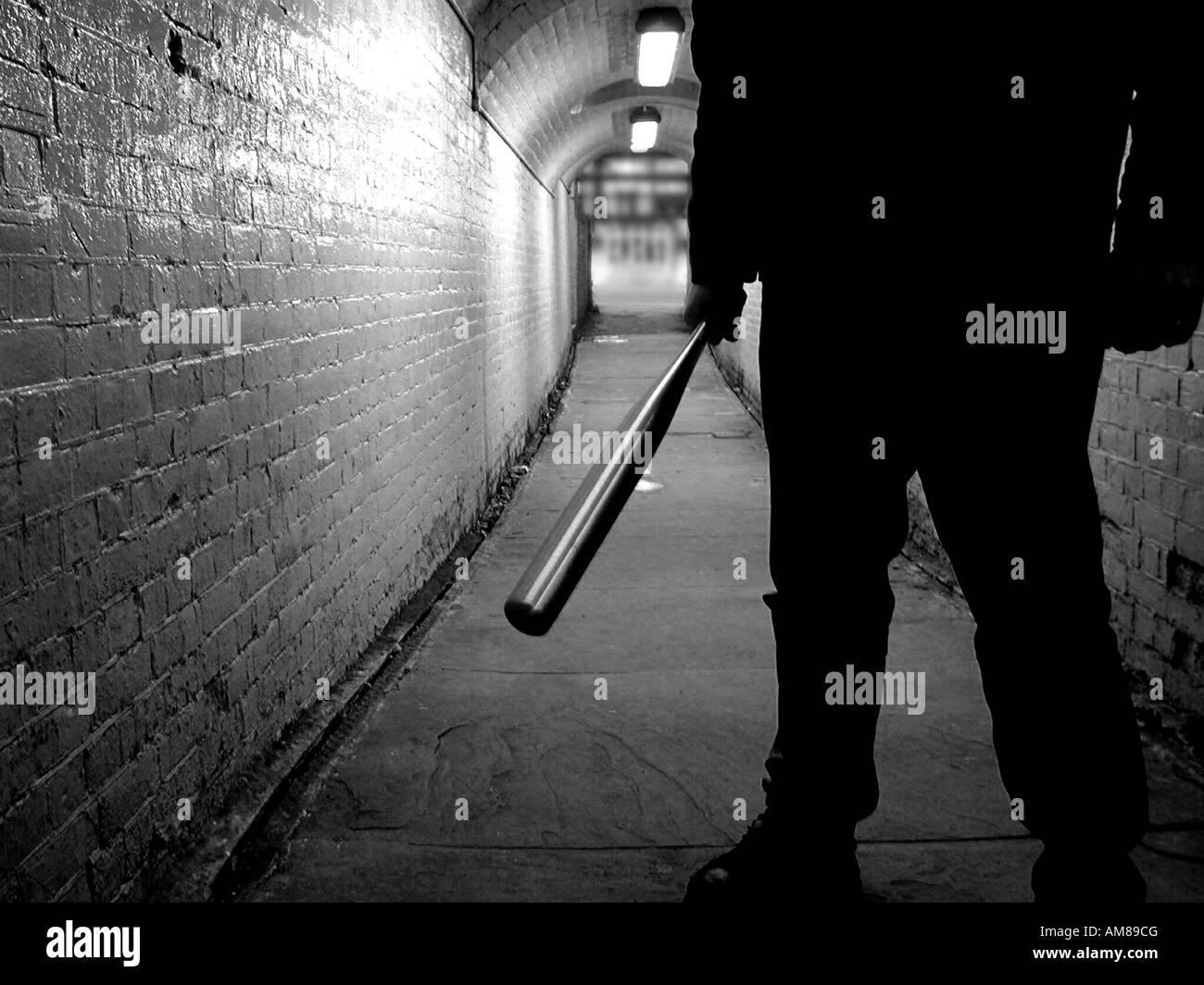 Unidentified thug with a baseball bat in a tunnel, black and white - Stock Image
