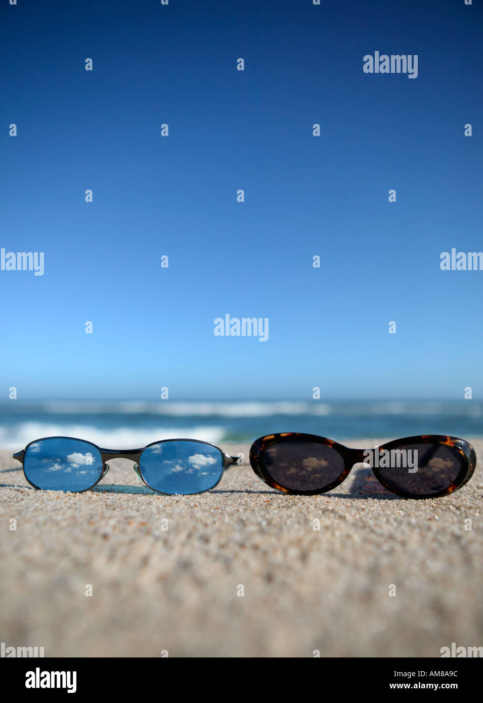 Two glasses laying on beach. - Stock Image